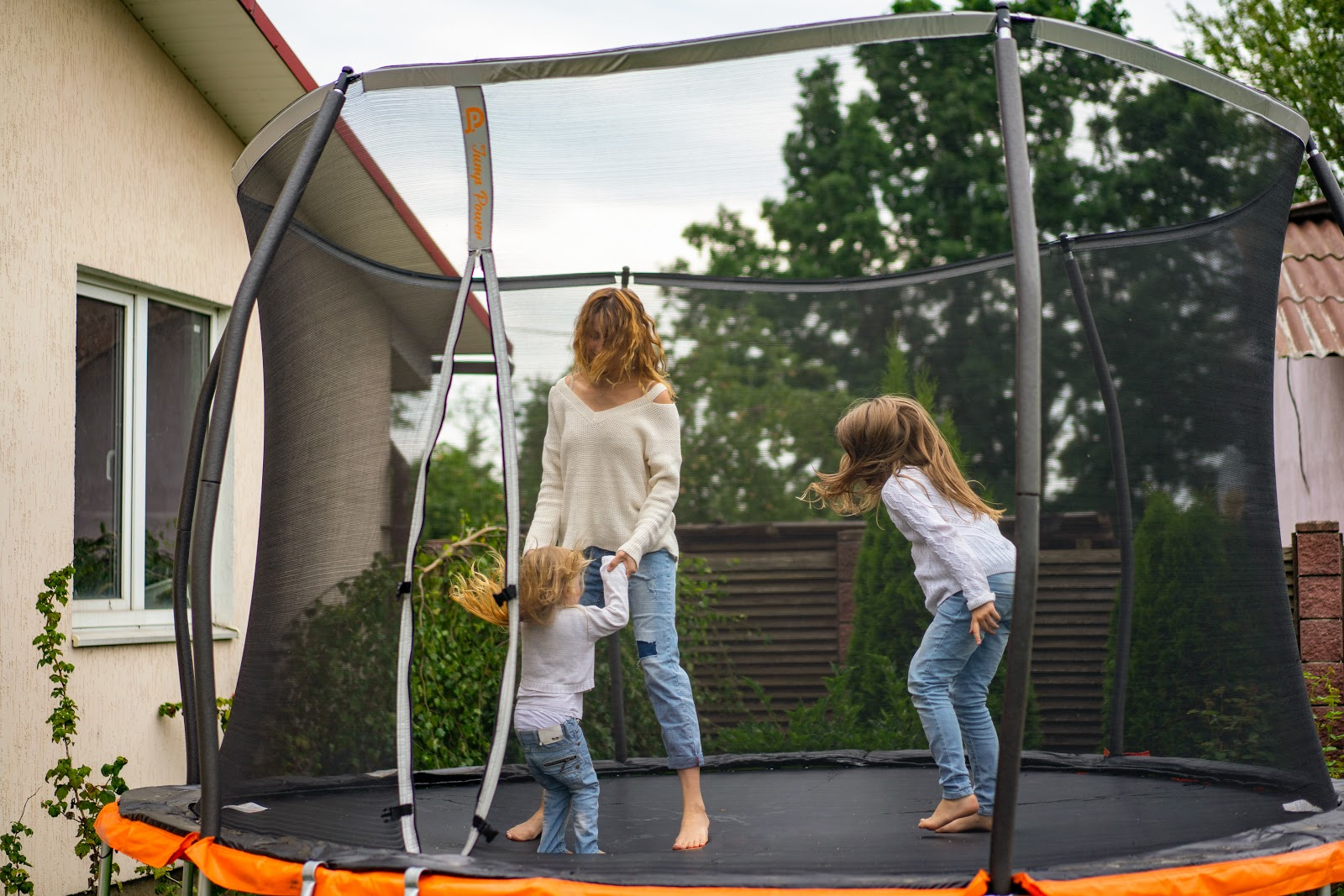 Photo of a mother with two daughters on a trampoline